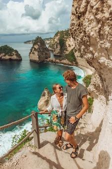Eine frau und ein mann stehen am diamond beach auf der insel nusa penida