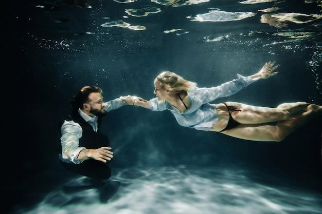 Eine frau und ein mann treffen sich unter wasser. ein paar liebende unter wasser.