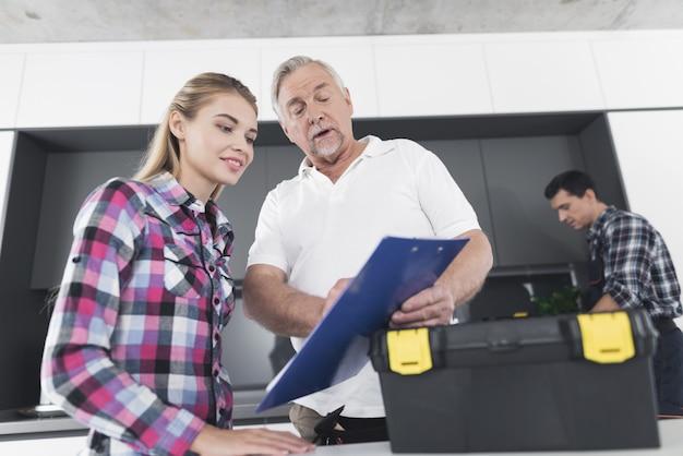 Eine frau unterschreibt ein formular für reparaturarbeiten durch klempner