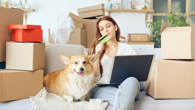 Eine frau verwendet einen laptop für online-shopping zu hause. kaufbestätigung durch das internet. binden einer karte für online-shopping. eine frau sitzt auf der couch mit einem süßen hund beim online-shopping.