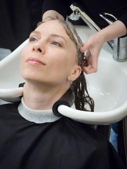 Eine frau wäscht sich nach einem haarschnitt in einem schönheitssalon die haare.