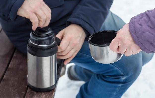 Eine frau wartet auf tee und hält eine tasse zu einer thermoskanne mit heißem tee.