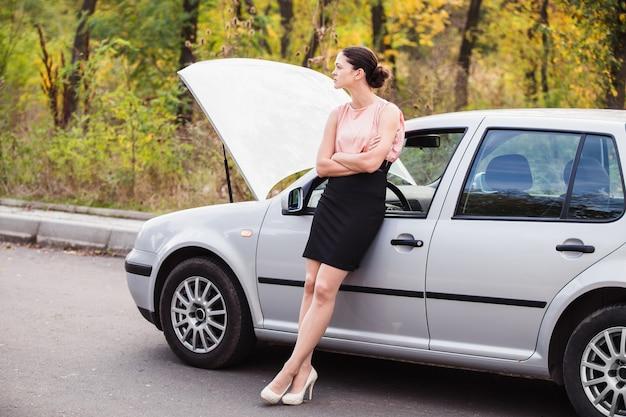 Eine frau wartet in der nähe ihres am straßenrand kaputten autos auf hilfe