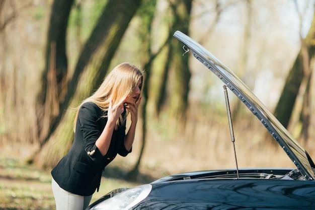 Eine frau wartet in der nähe ihres am straßenrand kaputten autos auf hilfe.