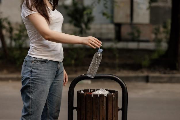 Eine frau wirft eine plastikflasche in einen hölzernen papierkorb in einem park. abfallrecycling