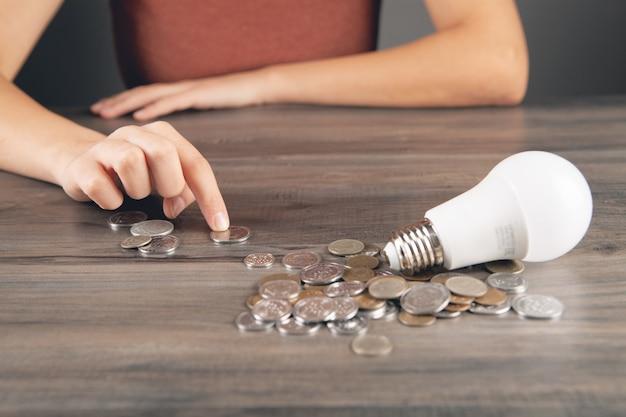 Eine frau zählt münzen und auf dem tisch liegt eine glühbirne