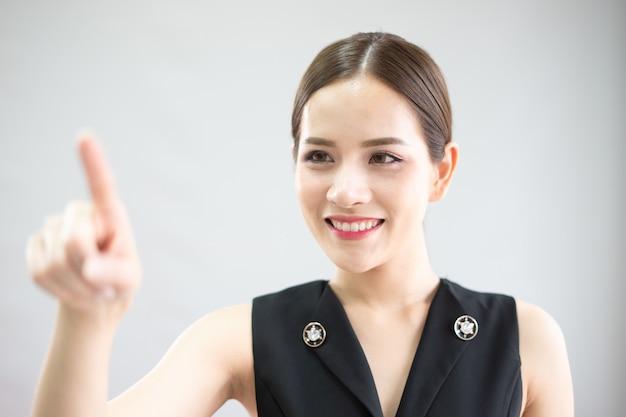 Eine frau zeigt auf den touchscreen. sie präsentiert die neue idee.