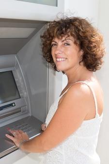 Eine frau zieht am banknotenautomaten geld ab