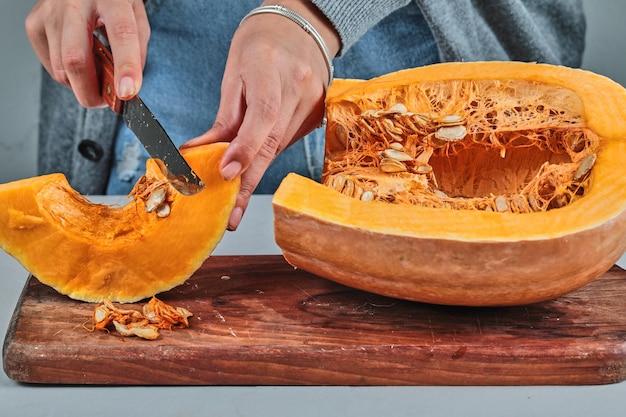 Eine frauenhand, die eine scheibe pumpkon mit messer auf holzbrett schneidet.