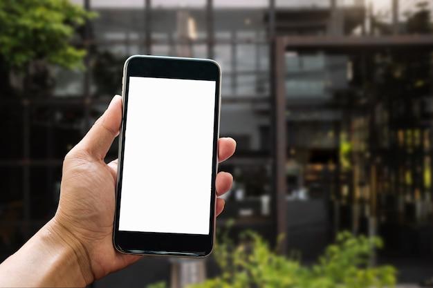 Eine frauenhand, die smartphone-gerät in der kaffeestube oder im caféhintergrund hält.