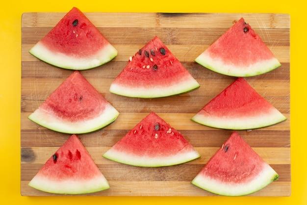 Eine frisch geschnittene wassermelone aus der draufsicht, weich und süß auf brauner holz- und gelber fruchtsommerfarbe