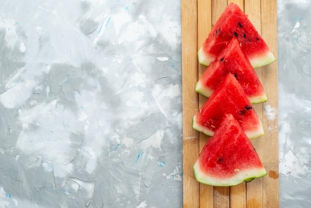 Eine frisch geschnittene wassermelone der draufsicht süß und weich auf brauner hölzerner und weißer fruchtsommerfarbe