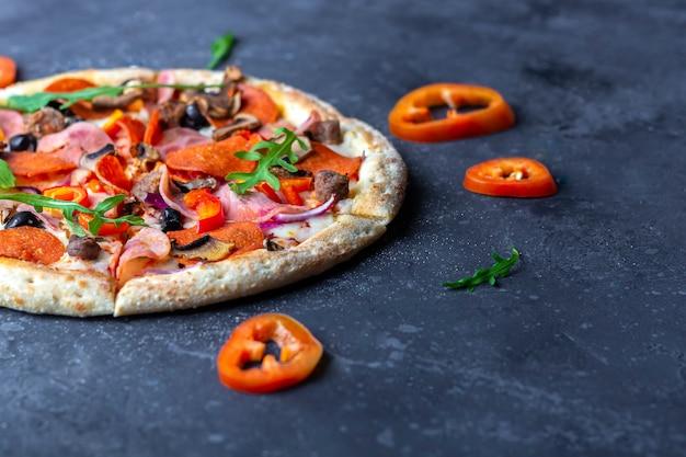 Eine frisch zubereitete pizza mit salami, pilzen, schinken und käse auf dunklem hintergrund. italienisches traditionelles mittag- oder abendessen. fast food und street food konzept. flach, draufsicht, kopierraum für text
