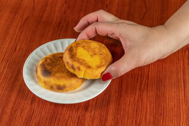Eine frische heiße arepa populär in kolumbien und venezuela aus zwei maiskuchen, die gebraten werden, bis der käse zwischen ihnen schmilzt, essen