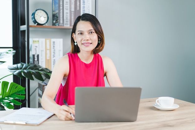 Eine fröhliche asiatische geschäftsfrau mittleren alters in entspannter freizeitkleidung, die zu hause arbeitet, e-mails auf computer-laptop überprüft und auf dokumentenpapier der finanzbuchhaltung schreibt. geschäft stockfotos
