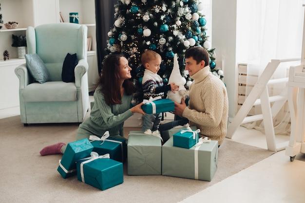 Eine fröhliche familie mit einem kleinen kind, das zusammen spaß nahe dem weihnachtsbaum hat