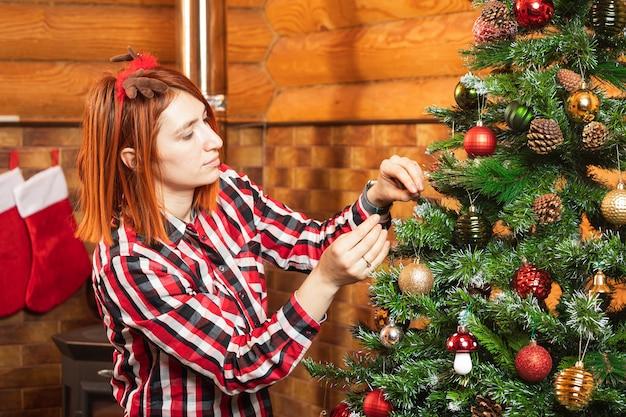 Eine fröhliche frau in einem karierten hemd hängt einen schönen glänzenden ball an einen weihnachtsbaum