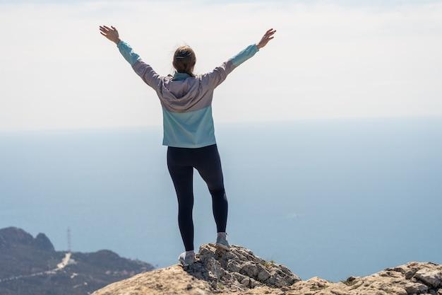 Eine fröhliche frau kletterte auf den höchsten felsen und blickt auf das grenzenlose blaue meer, atemberaubende vogelperspektive