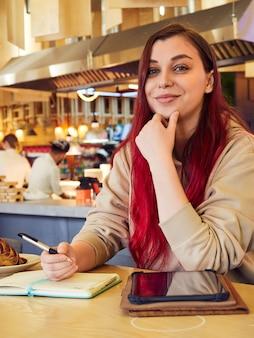Eine fröhliche frau mit roten haaren arbeitet fern in einem café und schreibt in ein tagebuch