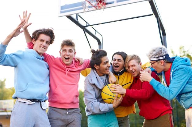 Eine fröhliche, fröhliche gruppe junger männer feiert ihre siegreichen, kaukasischen jungen, die sich gegenseitig gratulieren