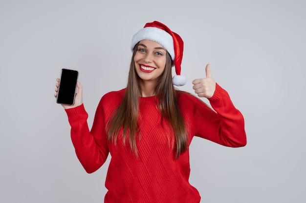 Eine fröhliche junge frau in einem roten pullover, die eine weihnachtsmütze trägt, zeigt ihre daumen hoch. das handy ist eingeschaltet. konzept für online-glückwünsche, verkäufe, einkäufe, rabatte.