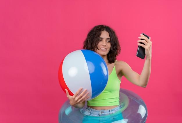 Eine fröhliche junge frau mit kurzen haaren im grünen erntedach, die lächelnd und aufblasbaren ball hält, der selfie mit handy nimmt