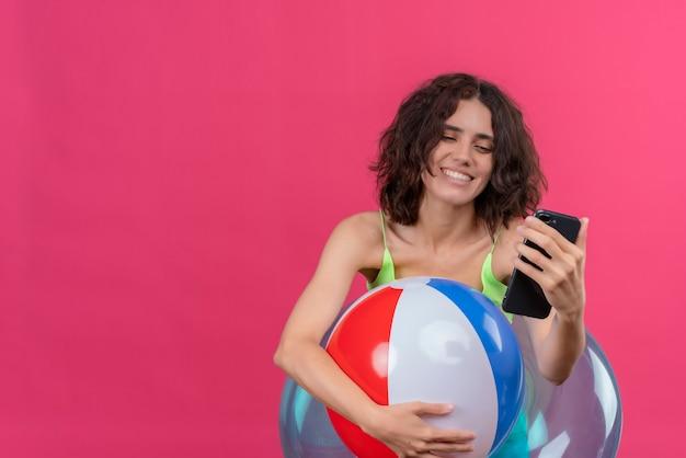 Eine fröhliche junge frau mit kurzen haaren in der grünen erntespitze, die aufblasbaren ball lächelt und das handy betrachtet