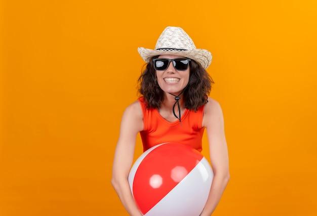 Eine fröhliche junge frau mit kurzen haaren in einem orangefarbenen hemd, das sonnenhut und sonnenbrille trägt, die aufblasbaren bunten ball umarmt