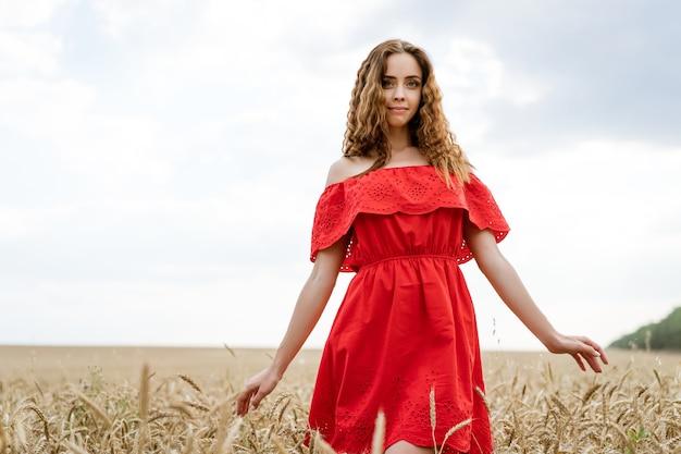 Eine fröhliche junge frau mit welligem haar in einem roten kleid steht auf einem feld mit weizen gegen einen blauen himmel während des tages