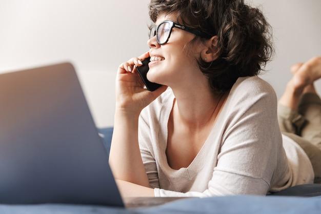 Eine fröhliche süße junge frau liegt drinnen auf dem bett und benutzt einen laptop, der mit dem handy spricht.
