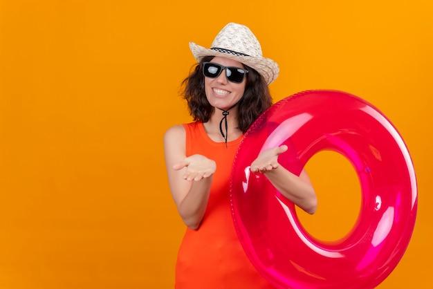 Eine fröhliche und erfreute junge frau mit kurzen haaren in einem orangefarbenen hemd, das sonnenhut und sonnenbrille hält, die aufblasbaren ring halten