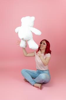 Eine fröhliche, verspielte frau mit roten haaren und jeans wirft einen großen weißen teddybär hoch
