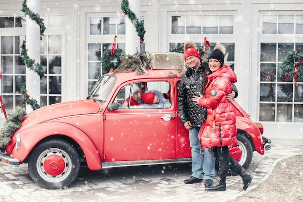 Eine fröhliche vierköpfige familie steht neben einem roten auto und freut sich