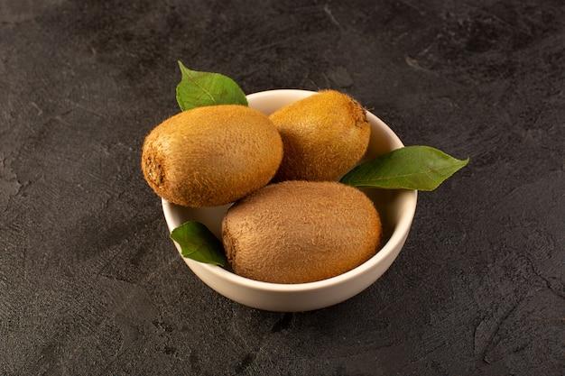 Eine front geschlossene ansicht braune kiwis frisch reif isoliert saftig weich und ganze früchte zusammen mit grünen blättern in weißen platte