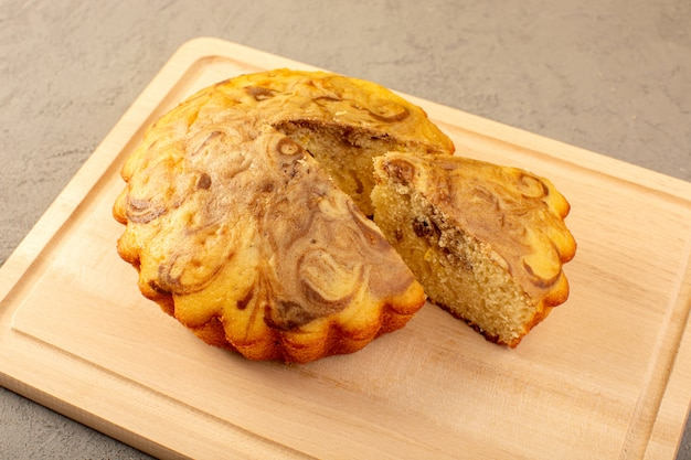 Eine front geschlossene ansicht süßen kuchen köstlichen leckeren schokoladenkuchen auf dem cremefarbenen quadratischen schreibtisch geschnitten