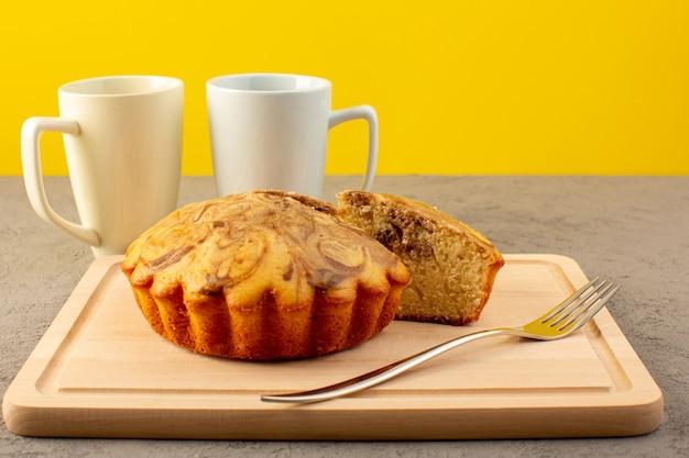 Eine front geschlossene ansicht süßen kuchen köstlichen leckeren schokoladenkuchen auf dem cremefarbenen quadratischen schreibtisch zusammen mit weißen tassen geschnitten