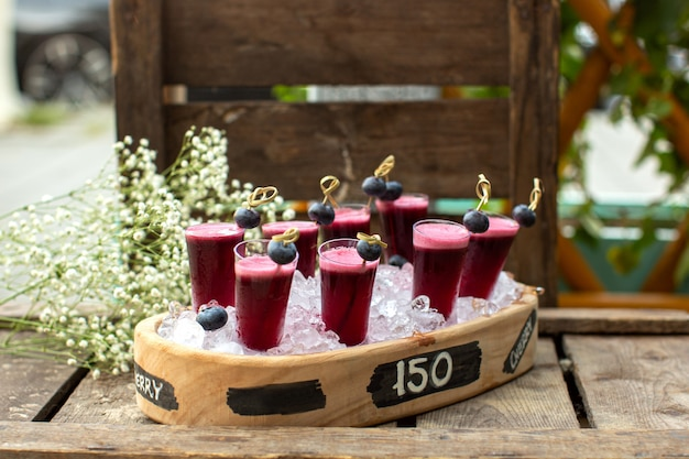 Eine front nahaufnahme ansicht cocktails burgunder frisch in braun schreibtisch auf dem holz rustikalen boden