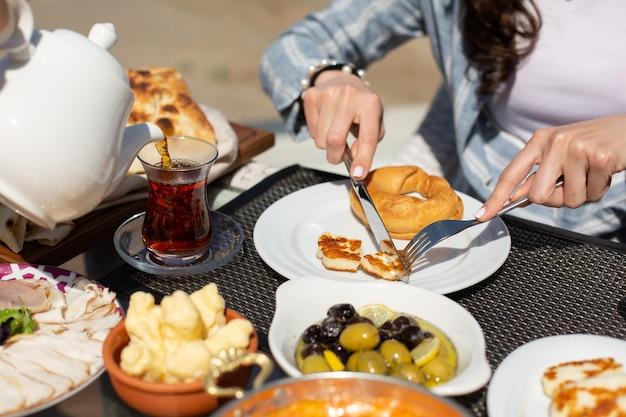 Eine frontansicht frühstückstisch menschen um tisch, die ihre mahlzeit während des tages essen tee frühstück