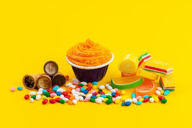 Eine frontansichtstorte und bonbons mit eishörnern und leckereien auf der gelben schreibtischfarbe bonbonfarbe