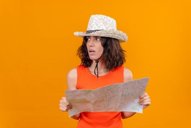 Eine frustrierte junge frau mit kurzen haaren in einem orangefarbenen hemd, das sonnenhut hält karte hält und rechte seite sucht, um weg zu finden