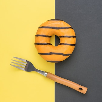 Eine gabel und ein glasierter donut auf einem gelben und schwarzen hintergrund. ein beliebter süßer snack.