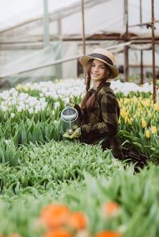 Eine gärtnerin mit hut und handschuhen gießt ein blumenbeet aus tulpen mit einer gießkanne