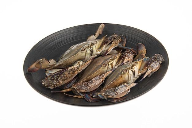 Eine ganz frische biologische krabbe wird auf einen schwarzen teller gelegt