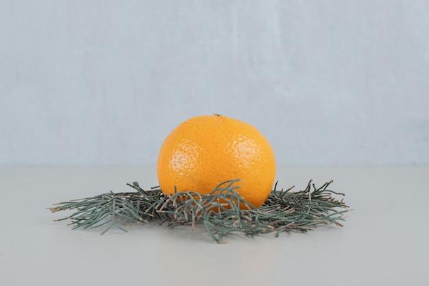 Eine ganze frische mandarine auf einem grauen hintergrund.