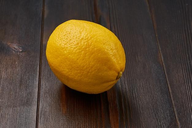 Eine ganze leuchtend gelbe reife köstliche bio-zitrone auf einem natürlichen holz