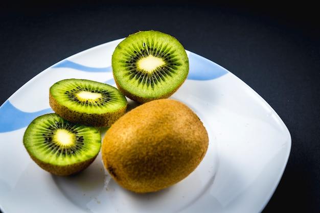 Eine ganze und zwei geschnittene kiwi auf einem weißen teller auf schwarz