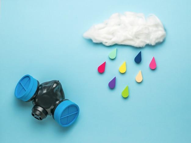 Eine gasmaske und eine wolke mit fallenden bunten tropfen auf einer blauen oberfläche