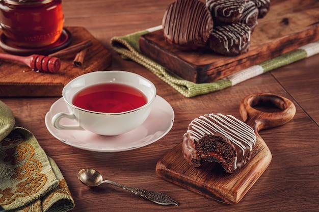Eine gebissene brasilianische honigplätzchenschokolade bedeckt auf dem holztisch mit einer porzellantasse tee, honigbiene und zimt - pao de mel