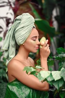 Eine gebräunte junge frau genießt nach einer dusche mit flecken unter den augen die natur.