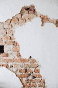 Eine gebrochene konkrete weiße wand mit ziegelsteinen